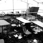 With the original school destroyed, villagers put up a tent to be used as a classroom. The desks, chairs, and blackboard were salvaged from the remains of the school.