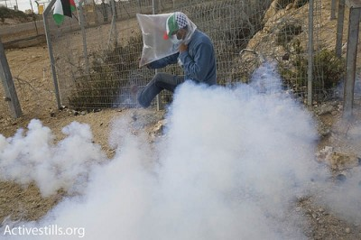 A Palestinian man kicks a tear gas grenade, shot by Israeli soldiers, during a mach against the apartheid wall in the West Bank village of Bi'lin, on January 1, 2010.