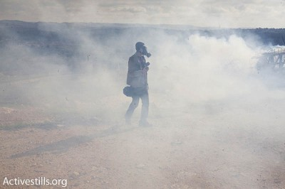 A photographer is seen inside a tear gas cloud, shot by Israeli soldiers, during a mach against the apartheid wall in the West Bank village of Bil'in, on January 1, 2010.
