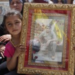 A Palestinian girl shows a photo of a relative held in Israeli jails.