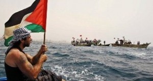 Vittorio waves the Palestinian flag on a boat off the coast of Gaza.