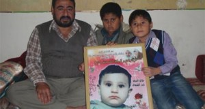 Jihad, Mu'tassam, and Zeid Nasla with a picture of M'uz Nasla, killed during the attack. (Photo: Palestinian Center for Human Rights)
