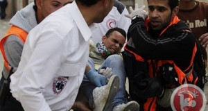 Medics carry an injured protester during clashes between protesters and Israeli  forces at a demonstration marking Land Day, at Qalandiya checkpoint Ramallah  on March 30. (Reuters/Darren Whiteside)