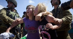 Israel soldiers holding back Nariman Tamimi's children as she is being arrested (Photo Courtesy of Oren Ziv - Activestills.org