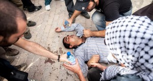 A demonstrator gets first aid help after being injured by a sound grenade at the protest