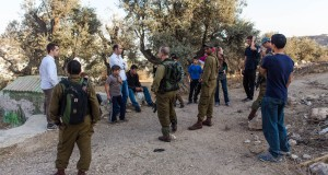A group of soldiers and international activists surround Ahmad after the settler attack