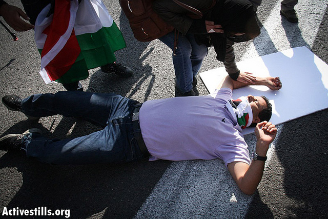 Abdallah Abu Rahmah lies injured on the ground after a car driven by Israeli settlers ran over him at a roadblock protest against Israel's military action in the Gaza Strip, November 19, 2012 Photo by: Guest photographer Hamde Abu Rahma / Activestills.org