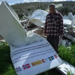 Mohammed Tomazi stands next to his destroyed home