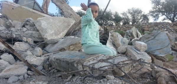A child sits on top of her demolished home