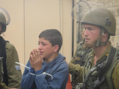 Detained child being taken to army jeep in Hebron.