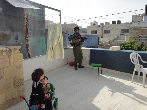Soldiers invade a Palestinian home, scaring children. Photo by ISM