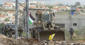 Israeli border police officers and armored bulldozer invading the village during a demonstration, April 2013 (Photo by ISM)