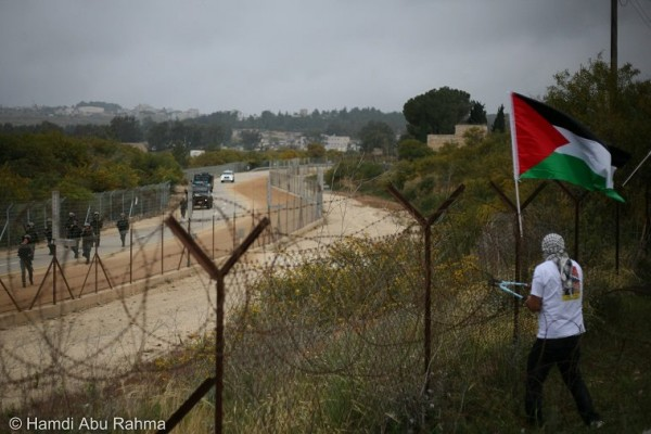 Army arrive as protesters cut down Apartheid Wall. Photo by Hamdi Abu Rahma
