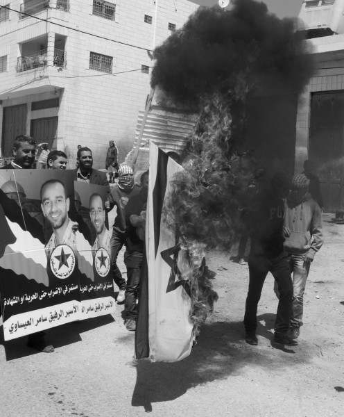 An Israeli flag is burned and placards of hunger strike Samer Issawi are held by demonstrators