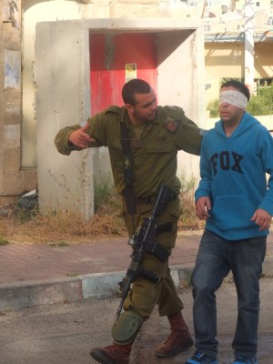 A man is blindfolded and led down Shuhada street by a soldier