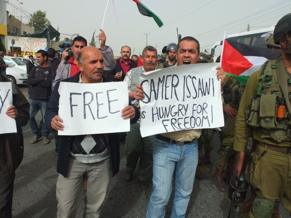 Demonstrators hold signs in support of hunger striker Samer Issawi
