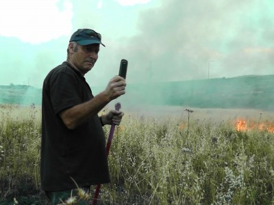 Illegal Shilo settler Moshka takes pictures of his handiwork, torching Palestinian land. (Photo by ISM)