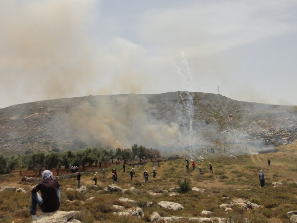 Tear gas being fired at demonstrators setting fires in the valley
