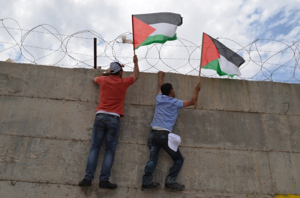 Protesters hang Palestinian flags on the wall (Photo by ISM)