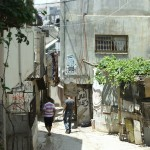 Two residents walk down a street in New Askar camp