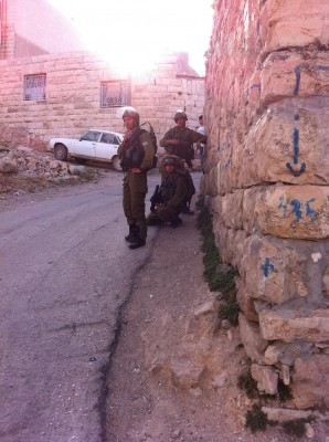 Soldiers hiding down a side-alley outside the school