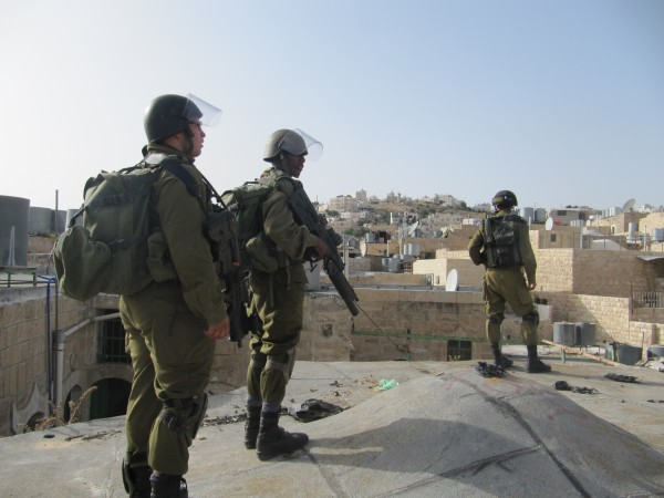 Soldiers invading the roof top of a Palestinian house (Photo by ISM)