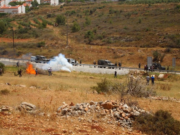 Israeli forces shoot tear gas canisters at protesters setting the land on fire (Photo by ISM)
