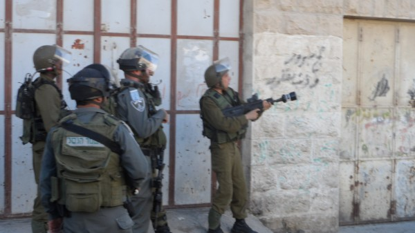 Israeli soldier shooting tear gas canisters (Photo by ISM)