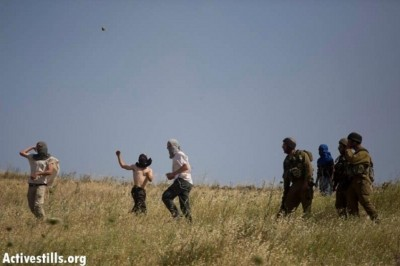 Settlers attack village residents as the Israeli army stand by . Photo: Activestills
