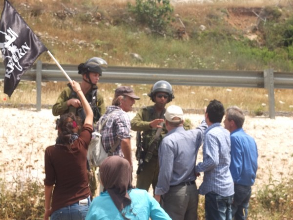 Residents of Nabi Saleh and Israeli activists argue with Israeli soldiers blocking the stolen well