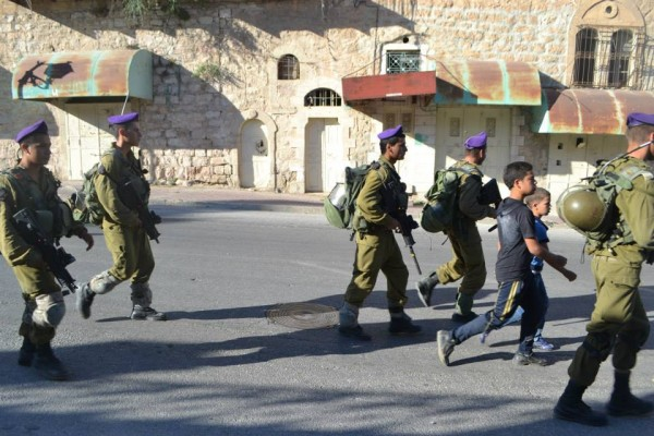 Soldiers escorting children down Shuhada Street