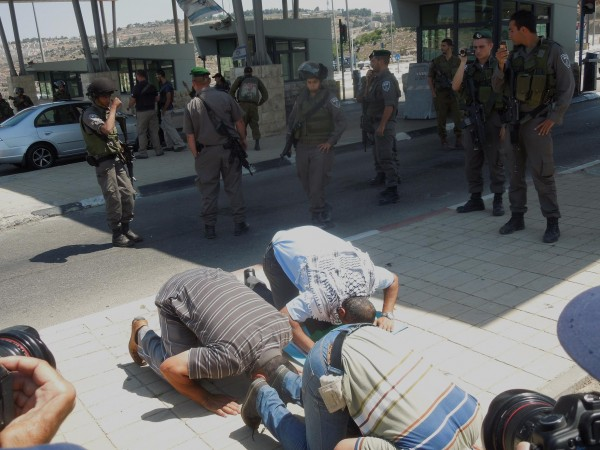 Protesters praying in front of the checkpoint to occupied Jerusalem