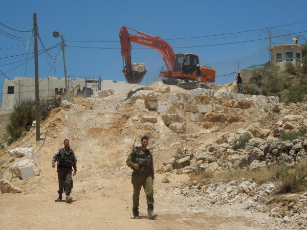 Israeli military guard bulldozer working on Palestinian land