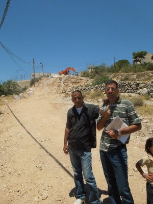 Palestinian landowners explain the destruction of their land (Photo by: ISM)