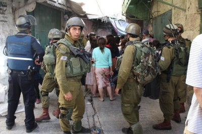 Settlers and soldiers block streets in the souq - restricting Palestinian movement - (Photo by ISM)
