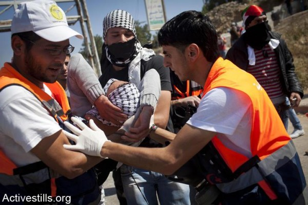 Palestinian medics evacuate a Palestinian youth after he was shot by Israeli soldiers during clashes at Ofer prison (Photo by Activestills)