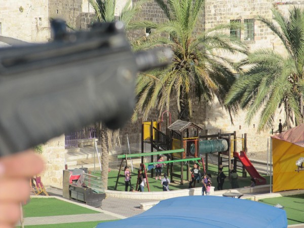 Soldier on rooftop pointing gun near playground - (Photo by ISM)