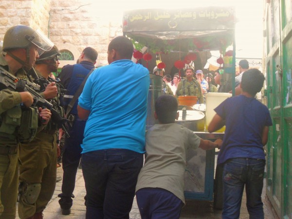 Palestinians try to take a juice stall through the souq, blocked by settlers and soldiers - (Photo by ISM)