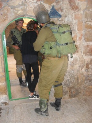 Activist blocks the door trying to prevent soldiers from entering