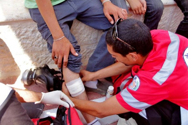 A medic treating an injured protester from rubber coated steel bullet in Nabi Saleh (Photo by Tamimi Press)