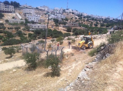 Bulldozers clear the path for the construction of the illegal settler road