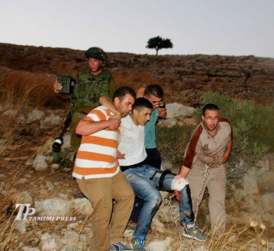 Mahmoud Tamimi being carried away after he was shot (Photo by Tamimi Press)