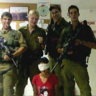Israeli soldiers posing for a photo with a female Palestinian arrestee blindfolded and handcuffed