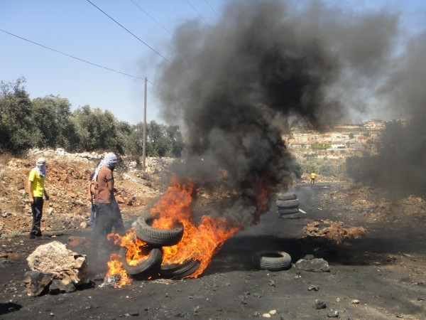 Tyre fires on the main blocked road to Nablus, with Qedumim illegal settlement visible in the background (Photo by ISM)