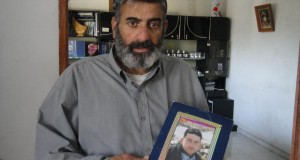 Abdallah's father with a picture of his imprisoned son (Photo by ISM)