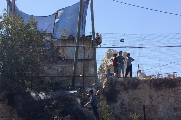 Israeli settler children stand laughing on the partially scorched wall just above their untouched plot of illegally cultivated land (Photo by Christian Peacemaker Teams)
