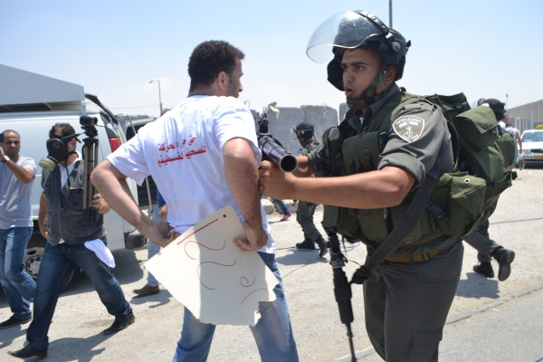 Israeli Border Police officer pushing back a journalist (Photo by ISM)