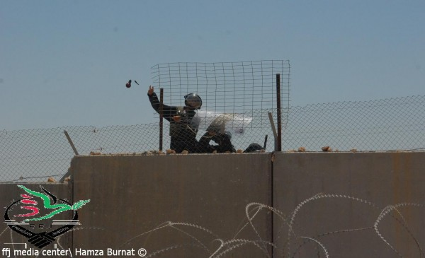 Israeli soldier throwing a tear gas canister at protesters (Photo by Hamza Burnat)