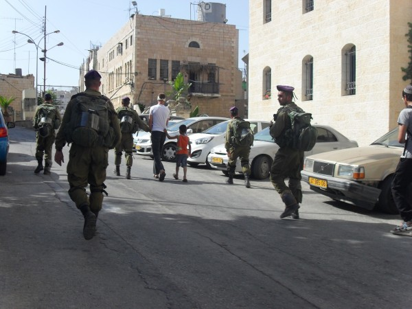 Israeli soldiers escorting Abu karem and his son to checkpoint 56 (Photo by ISM)