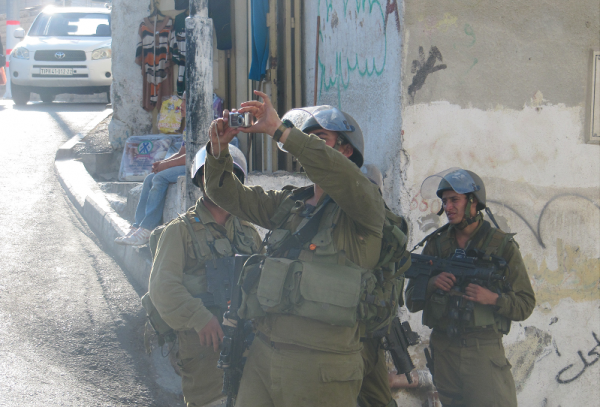 Israeli soldiers taking photos of children (Photo by ISM)